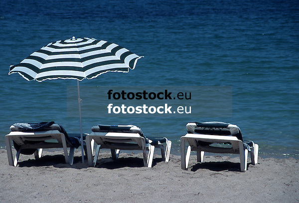 three reclining chairs and an umbrella at a sandy beach<br /> <br /> tres hamacas y un parasol en la playa<br /> <br /> drei Sonnenliegen und ein Sonnenschirm am Sandstrand<br /> <br /> 3000 x 2037 px<br /> Original: 35 mm slide transparency