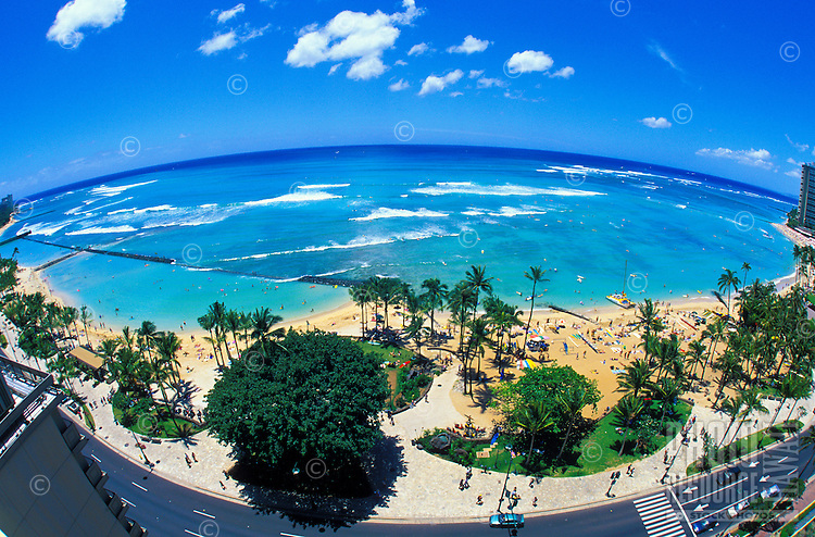 View of renowned Waikiki Beach with it's warm sands, blue waters, resort hotels and swaying palm trees.