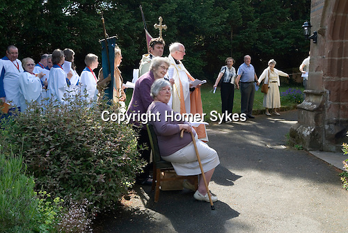 """Church Clipping Ceremony St Peters Church, Edgmond, Shropshire Uk 2015. <br /> The congregation hold hands, in a circle around the whole of the church, if they can, they did just in 2015, with the use of belts and ropes to complete the unbroken circle.  <br /> The Revd Prebendary Edward Ward and father Mark Chadwick.<br /> <br /> The word """"clipping"""" is Anglo-Saxon in origin, and is derived from the word """"clyp-pan"""", meaning """"embrace"""" or """"clasp"""" and thus is an expression of devotion."""