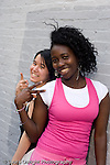 Education High School  senior students posing and having fun outside school building two girls posing making hand signs gestures vertical