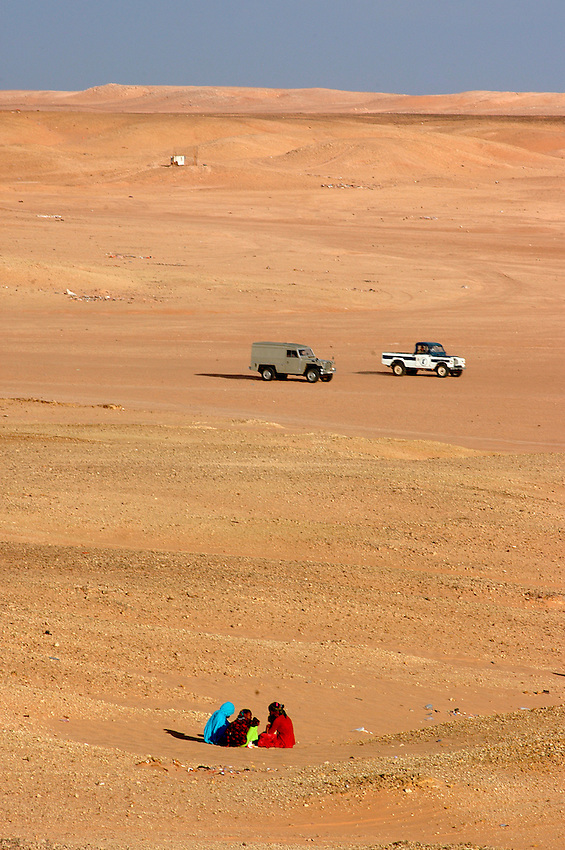 People sit on the desert on December 12, 2003, in the Saharawi refugee camps. Saharawi people have been living at the refugee camps of the Algerian desert named Hamada, or desert of the deserts, for more than 30 years now. Saharawi people have suffered the consecuences of European colonialism and the war against occupation by Moroccan forces. Polisario and Moroccan Army are in conflict since 1975 when Hassan II, Moroccan King in 1975, sent more than 250.000 civilians and soldiers to colonize the Western Sahara when Spain left the country. Since 1991 they are in a peace process without any outcome so far. (Ander Gillenea / Bostok Photo)