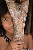Xingu Indigenous Park, Mato Grosso State, Brazil. Barranco Alto (Kaiabi). Shy girl with tortoise design tukum nut necklaces.