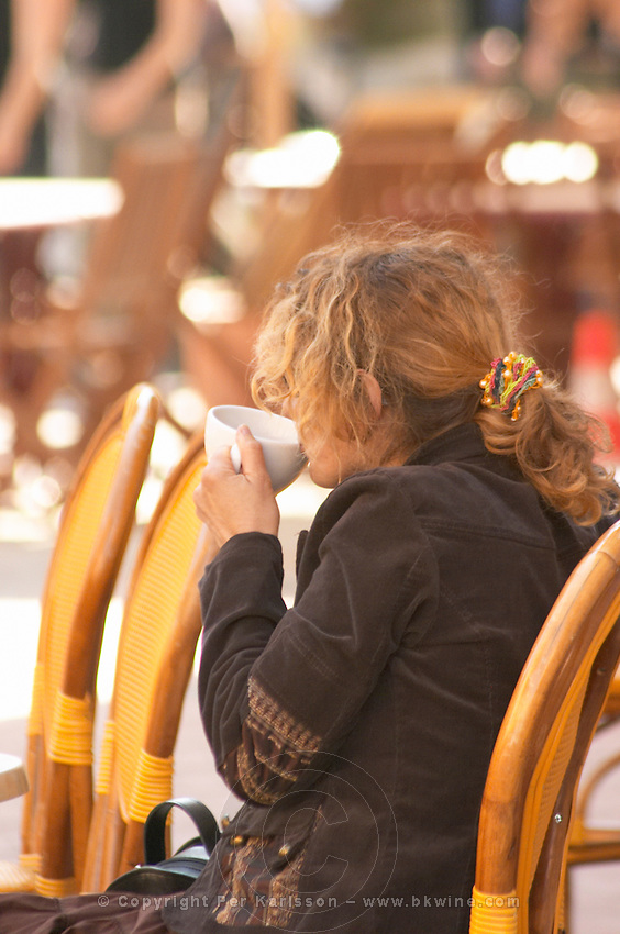Cafe scene outdoor terrace in the old town, a young woman alone in big curly red hair drinking a cup of cafe au lait caffe latte, sitting on a wicker chair looking the other way, dressed in brown and a chequered skirt, running shoes Sanary Var Cote d'Azur France