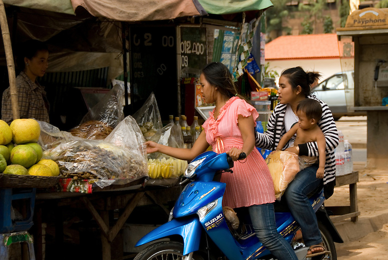 There is a stark contrast visible as increased wealth makes its way into the cities of Southeast Asia but bypasses the rural areas. A Siem Reap family of three shop by motorbike in the market.  Cambodia has one of the highest motorbike fatality rates among the Association of Southeast Asian Nations, or ASEAN. Helmet rules are slowly making their way into Cambodia culture as the increased use of motorbikes has also meant that the fatalities caused by crashes has nearly doubled in a 5 year period.