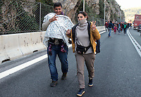 Pictured: A young family of migrants walk on the motorway Thursday 25 February 2016<br /> Re: Hundreds of migrants, including families with young children, that were stranded at Tempe in central Greece, were forced to walk on foot on the motorway to reach Idomen, about 168 kilometres away, in the northern part of the country, at the Greek FYRO Macedonian border. Local police were at first escorting them, then made sure that they were safely transported on coaches.