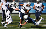 BYU's Paul Lasike (33) runs against Nevada defenders Alex Bertrando (56) and Matthew Lyons (9) during the first half an NCAA college football game in Reno, Nev., on Saturday, Nov. 30, 2013. (AP Photo/Cathleen Allison)