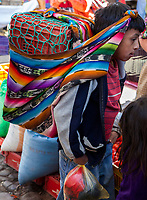 Chichicastenango, Guatemala.  Young Boy Carrying the Family Purchases in the Market.