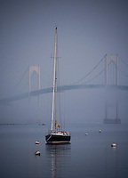 A sailboat sits alone in the fog