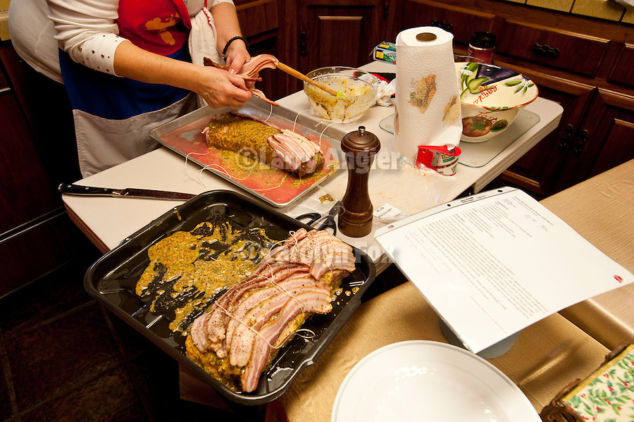 Christmas Day celebration with Jackson's Serbian community...Lana Vukovich prepares a traditional bacon-wrapped Serbian pork roast for her Christmas guests in the kitchen.