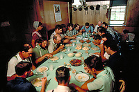 Conservative Mennonite men and a few Amish are served lunch at the long dining table at the Mennonite homestead. Women serve food during a day long barnraising when a barn is built in one day. Mennonite and Amish farmers. Lancaster Pennsylvania United Sta