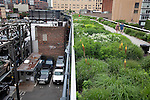 A view of a car park at left and the High Line at right which is a public park built on a 1.45-mile-long elevated rail structure running from Gansevoort Street to West 34th Street on Manhattan's West Side, New York City.
