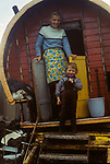 Irish Travellers, family mother and son, Belfast 1969. Northern Ireland. Traditional horse drawn caravan. 1960s UK. Bow top wagon with wooden spoke wagon wheels.
