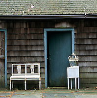 A Swedish bench and lantern infront of a shed with a blue door