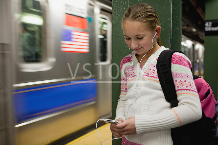 USA, New York State, New York City, Girl (10-11) standing at subway station with earphones and listening music