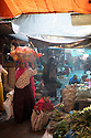 India - Manipur - Imphal - A seller carries fresh vegetables on her head through the aisle of the Ima Market.
