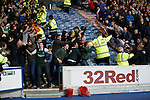 Hibs fans spill out onto the track as they celebrate the opening goal at Ibrox