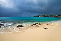 Paradisiac, white sand beach rocks, turquoise water, and seafront under a cloudy sky, in Sint Maarten (Saint Martin), Caribbean Leeward Islands