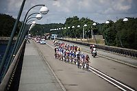 As the peloton hits the bridge over the Lacs de l'eau d'Heure the wind blows (from the left) the peloton in 2 echelons. Race leader (yellow jersey) Niki Terpstra (NLD/Etixx-QuickStep) is about to cross from the 2nd into the first echelon at this point. The echelon has no further influence on the race as the wind subsides as soon as they leave the (long) bridge. <br /> <br /> Tour de Wallonie 2015<br /> stage 5: Chimay - Thuin (167km)