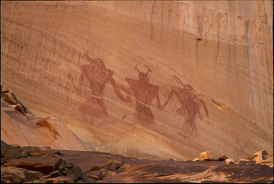 """""""Calf Creek Pictographs""""<br /> Grand Staircase / Escalante National Monument<br /> 2004<br /> <br /> While hiking down the trail along Calf Creek Canyon toward the falls, people can view a magnificent wall on the northeast side of the creek.  Toward the bottom of the wall, if one looks close enough, you can spot a nice example of pictographs in the typical Fremont style of rock art.  We hiked across the canyon to get a close up view of the figures.  What do they represent?  No one knows for sure.  Could it be family?  If you look close, you can even see what might be the family dog. One thing for sure, many people have created their own interpretation while pausing along this pleasant hike."""