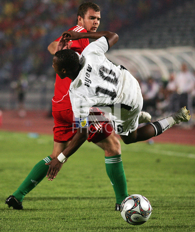 Ghana's Andre Ayew (10) falls to the ground after tangling with Hungary's Andras Debreceni (5) after fighting for a header during the FIFA Under 20 World Cup Semi-final match at the Cairo International Stadium in Cairo, Egypt, on October 13, 2009. Costa Rica won the match 1-2 in overtime play. Ghana won the match 3-2.