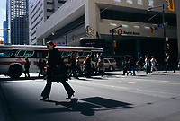 A pedestrian cross the street in front of the Bank of Montreal building on King Street West<br />  in downtown Toronto, April 20, 2007<br /> .   photo by Pierre Roussel - Images Distribution