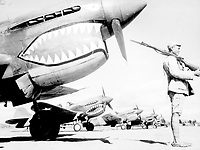 """""""A Chinese soldier guards a line of American P-40 fighter planes, painted with the shark-face emblem of the `Flying Tigers,' at a flying field somewhere in China."""" Ca. 1942."""