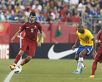 Portugal forward Nelson Oliveira (9) dribbles.  In an international friendly, Brazil (yellow/blue) defeated Portugal (red), 3-1, at Gillette Stadium on September 10, 2013.