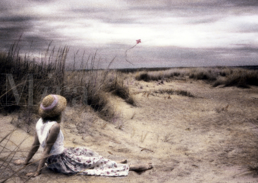 Woman in dunes watching kite overhead. Hand-tinted look.
