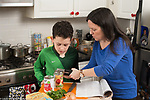 10 year old boy cooking in kitchen at home, watching mother demonstrate how to use can opener