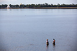 18 JUNE 2015, Mandalay, Myanmar:  Fishermen in the water beneath  the U Bein Bridge; a crossing that spans the Taungthaman Lake near Amarapura in Myanmar. The 1.2-kilometre bridge was built around 1850 and is believed to be the oldest and longest teakwood bridge in the world. <br /> The bridge was built from wood reclaimed from the former royal palace in Inwa. It features 1,086 pillars that stretch out of the water, some of which have been replaced with concrete. Though the bridge largely remains intact, there are fears that an increasing number of the pillars are becoming dangerously decayed. Some have become entirely detached from their bases and only remain in place because of the lateral bars holding them together. Picture Graham Crouch/The Australian Magazine