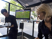 France. Paris. A couple of waiters, a man and a woman, serving at a cafe on the Georges V avenue. On the flat screen of a Panasonic television, the french tv channel TF1 is broadcasting a soccer match from the World Cup 2010. 11.06.10 © 2010  Didier Ruef