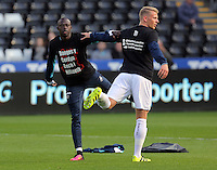 (L-R) Modou Barrow and Stephen Kingsley of Swansea City wearing Show Racism Red Card before the Premier League match between Swansea City and Watford at The Liberty Stadium on October 22, 2016 in Swansea, Wales, UK.