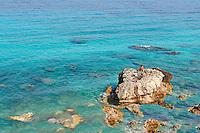 A Fisherman on the rocks of Pefkoulia in Lefkada, Greece