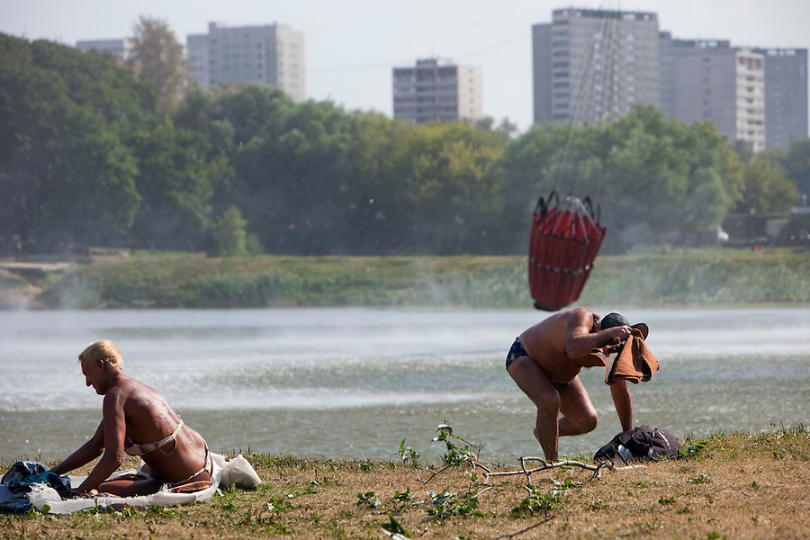 Moscow, Russia, 15/07/2010..Sunbathers in a Moscow park take cover as Emergency Ministry helicopters suddenly arrive to collect water while fighting a fire that killed two at a nearby art restoration centre.