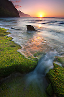 At sunset, a wave rushes over algae-covered rocks at Ke'e Beach, Kaua'i.