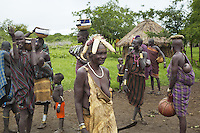 """Ethiopia. Southern Nations, Nationalities, and Peoples' Region. Omo Valley. Mursi tribe. Village and huts. Agro-pastoralist group. Nomadic. A group of Mursi women and children. Mursi women are known as """"disk-lip"""" women. The bottom lip is slit along its full length and the front bottom row of teeth are pulled out to accomodate the ceramic disk which is handmade with a rim around which the stretched lip is pulled. The women are famed for wearing large plates in their lips (round clay plates placed into a cut in the lower lip) and ears. The disk is seen as a symbol of beauty and wealth, and often the younger girls will pierce and strech their ear-lobes, inserting a matching disk in the extended lobe. The Omo Valley, situated in Africa's Great Rift Valley, is home to an estimated 200,000 indigenous peoples who have lived there for millennia. Amongst them are 8'000 Mursi who dwell between the Omo and Mago rivers. Southern Nations, Nationalities, and Peoples' Region (often abbreviated as SNNPR) is one of the nine ethnic divisions of Ethiopia. 11.11.15 © 2015 Didier Ruef"""
