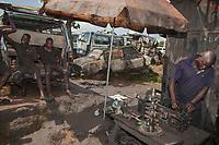 Nigeria. Enugu State. Enugu. Open Air Garage. Workshop. Mechanics at work on an engine. Sunshade and cars wrecks. Enugu is the capital of Enugu State, located in southeastern Nigeria. 4.07.19 © 2019 Didier Ruef