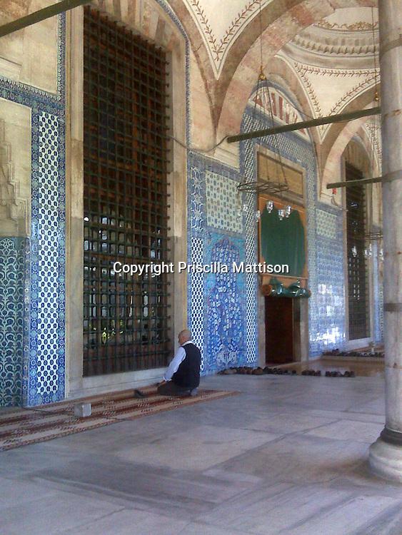 Istanbul, Turkey - September 23, 2009:  A man kneels outside Rustem Pasa Mosque.