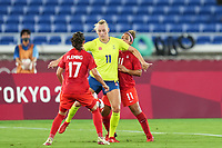 YOKOHAMA, JAPAN - AUGUST 6: Stina Blackstenius #11 of Sweden battles for the ball against Jessie Fleming #17 of Canada and Desiree Scott #11 of Canada during a game between Canada and Sweden at International Stadium Yokohama on August 6, 2021 in Yokohama, Japan.