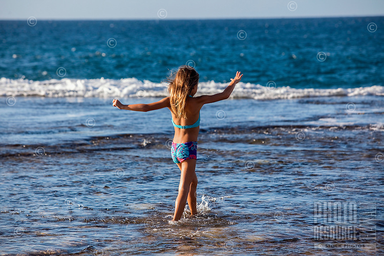 A young girl walks on a reef at a North Shore beach on O'ahu.