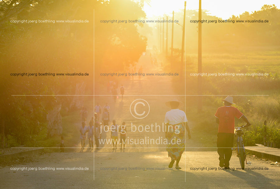 MADAGASCAR, Mananjary, walking people in sunlight / MADAGASKAR Mananjary, spazierende Menschen im Abendlicht