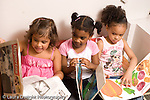 Preschool ages 3-5 three girls sitting side by side looking at books  horizontal