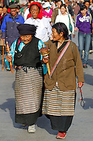 Tibetan Buddhists, with prayer wheels and rosary beads, walking the Barkhor pilgrim circuit around the Jokhang Temple during the Saga Dawa festival, Lhasa, Tibet.