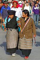 Tibetan Buddhists, with prayer wheels and rosary beads, walking the Barkhor pilgrim circuit around the Jokhang Temple during the Saga Dawa festival, Lhasa, Tibet.