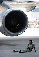 An employee of Taiko Aircraft Engineering Company rests near one of the jet engines of a 747 cargo plane in Xiamen, China..