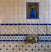 Stainless steel shower taps against a wall of geometric blue and white tiles