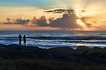 Sun sinks into rain clouds over Yachats Beach, on the central Oregon coast.  Three people in siloughouette.