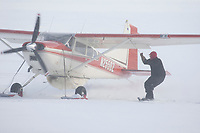 Eagle Island lead checker Jim Gallea helps pilot Bruce Moroney turn his plane by holding the strut rope at the Eagle Island checkpoint during Iditarod 2009
