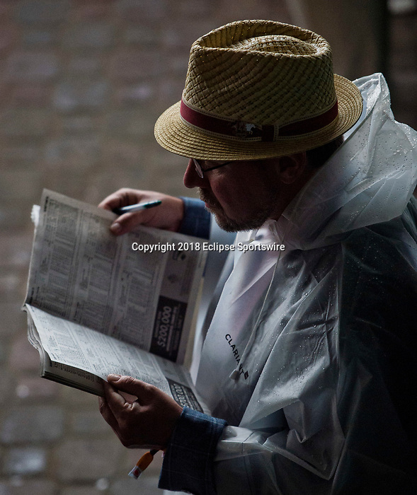 LOUISVILLE, KY - MAY 05: A man hides from the rain and reads a program on Kentucky Derby Day at Churchill Downs on May 5, 2018 in Louisville, Kentucky. (Photo by Scott Serio/Eclipse Sportswire/Getty Images)
