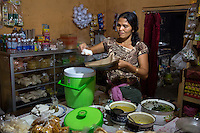 Bali, Indonesia.  Woman Making Breakfast Packets in her Home for Customers, Babakan Village.  Placing Rice in a paper Holder.